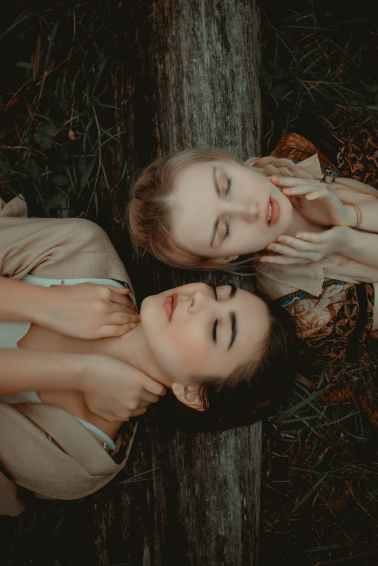 photo of two women lying on grass